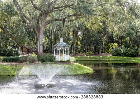 A white gazebo by an old oak tree draped in spanish moss with a fountain and lake - stock photo