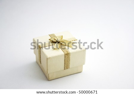 A white gift box or jewelry box with gold ribbon bow-knot. - stock photo