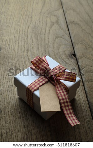A white gift box with closed lid, tied to a bow with red and cream gingham ribbon.  Blank vintage label facing upwards.  - stock photo