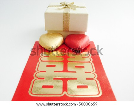 A white gift or jewelry box with two heart shape candy and a Chinese double happiness red packet. - stock photo