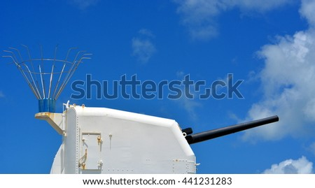 A white gun turret with black barrel against a blue sky with clouds. - stock photo