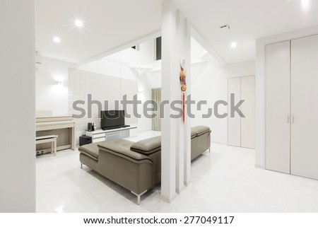 A white interior with leather sofa, internet TV, piano on the marble. - stock photo