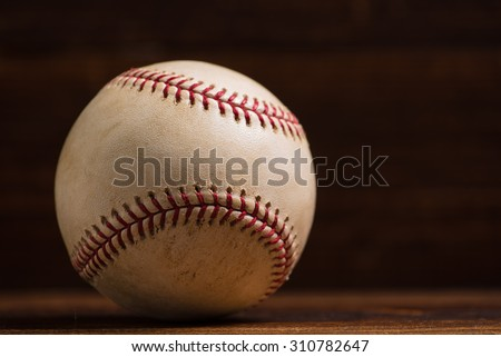 A white leather baseball on a wooden bench background - stock photo