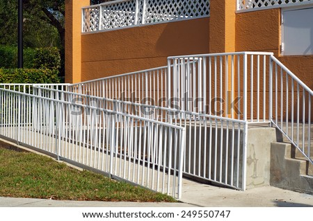 A white metal railing encloses a handicap ramp leading up to a building in Naples, Florida. - stock photo