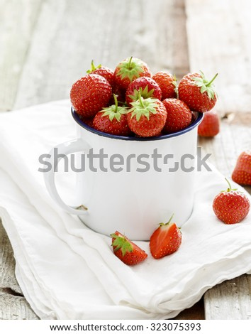A White mug filled with succulent juicy fresh ripe red strawberries on an old wooden textured table top - stock photo