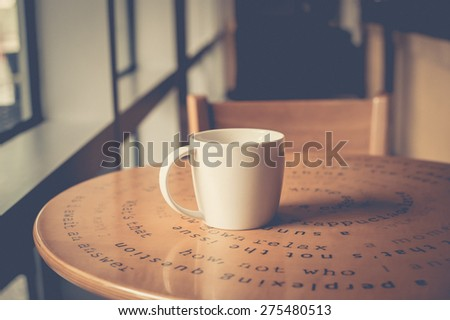 A white mug of coffee on table near window in cafe restaurant. Vintage filter. - stock photo