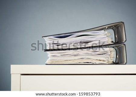 A white office desk with two folders full with paperwork lying on top of it. - stock photo