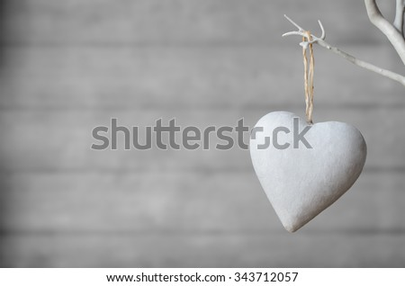 A white painted heart, hanging from branch of white artificial tree, with neutral  wood plank soft focus background. - stock photo