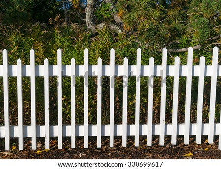 A white painted wood border fence with scrub brush in the background. - stock photo