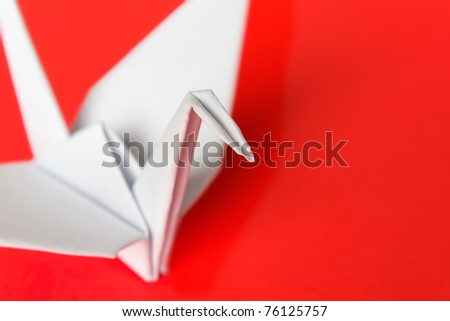 A white paper bird on a red background, shallow depth of field - stock photo