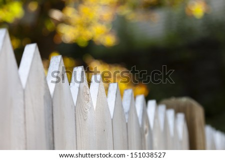 A white picket fence with short focus and an autumn background. - stock photo
