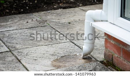 A white plastic PVC downspout spilling out onto a patio - stock photo