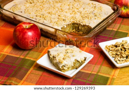 A white plate with a slice of apple cake and apple - stock photo