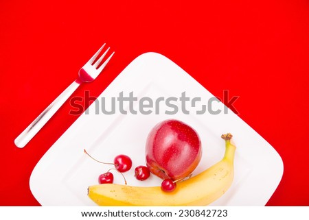 A white plate with fruit on red background.  - stock photo