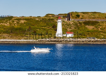 A white pleasure boat speeding past a lighthouse in blue water - stock photo