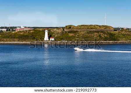 A white speedboat in blue water approaching a white lighthouse - stock photo