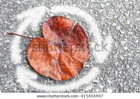 A white spray paint recycle arrow around a browning leaf for the concept of recycle to save the environment. - stock photo