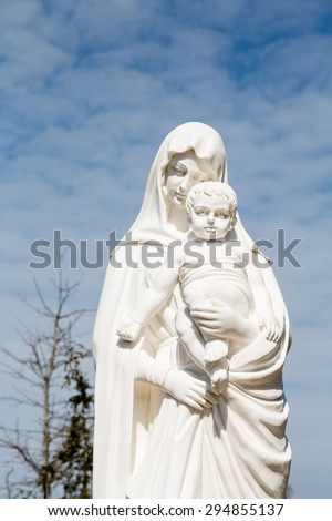 A white stone statue of the Madonna and Jesus under nice sky - stock photo