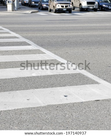 A white street crossing at a busy intersection. - stock photo