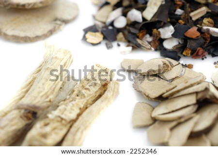 A white surface scattered with plant materials and herbs prepared by a traditional chinese herbalist for medical purposes - stock photo