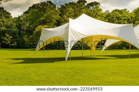 A white tent or marquee in a green field. - stock photo