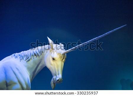 A white unicorn against blue wall - stock photo
