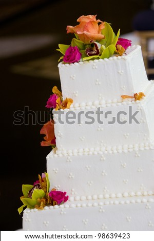 A white wedding cake with multiple layers and flowers. Wedding details. - stock photo