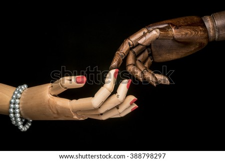 A white woman's hand and a black man's hand touching the tip of a finger. On black background. - stock photo