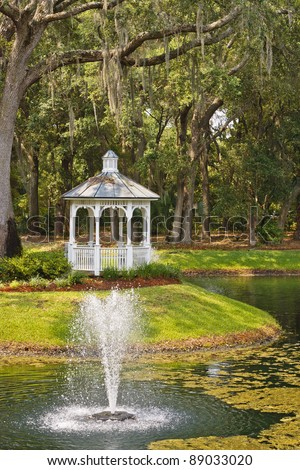 A white wood gazebo in the woods with a fountain in a lake - stock photo