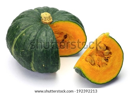 A whole acorn squash with a wedge cut from it. - stock photo