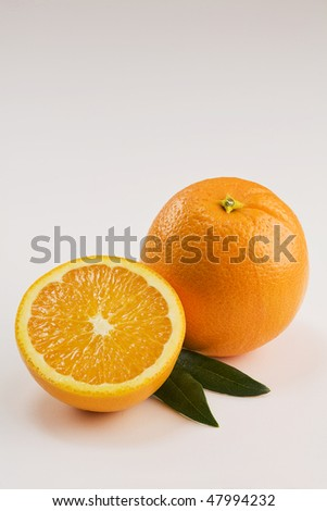 A Whole and a Half Orange Isolated on White with Leaves Vertical - stock photo