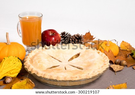 A whole apple pie with apple cider and gourds on the side. - stock photo