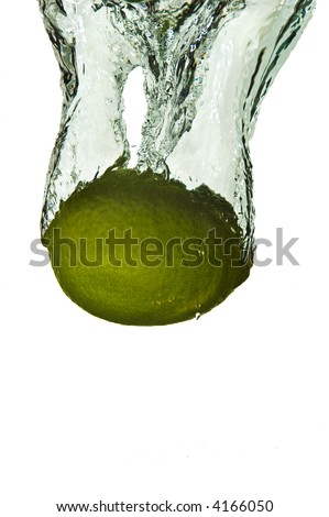 A whole lime plunged into water on a white background - stock photo
