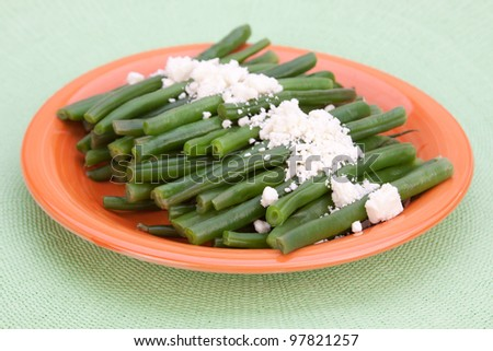 A whole plate of fresh, steamed, organic green beans, sprinkled with feta cheese. - stock photo