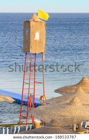 A wicker lifeguard watchtower or lookout tower and yellow flag on a beach. - stock photo