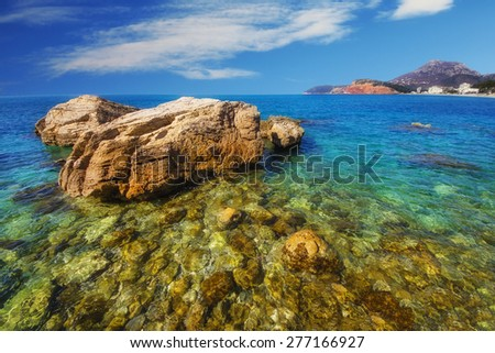 A wide angle shot of a rock in the sea, Sutomore beach, Montenegro - stock photo