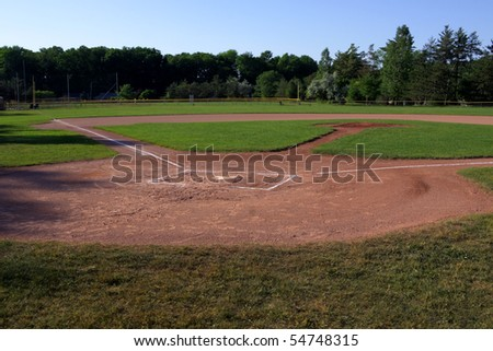 A wide angle shot of an unoccupied baseball field.  The shot was created via HDR. (multiple exposures combined) - stock photo