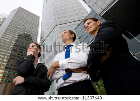 A wide angle shot of businesswomen and businessman and skyscrapers - stock photo