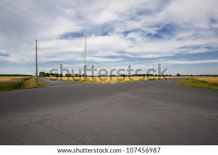 A wide angle view of a rural intersection framed in wheat fields with a beautiful dramatic sky above. - stock photo