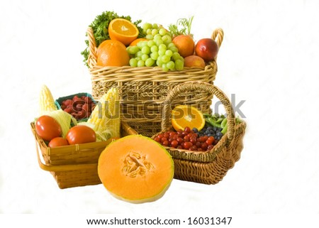 A wide selection of organic produce in baskets over a white background. - stock photo