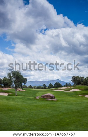 A wide shot looking down a golf fairway to the green. - stock photo