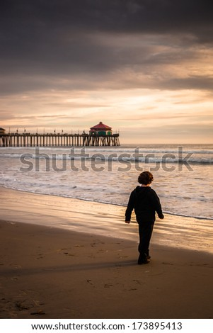 A wide shot of a winter sunset looking out to Catalina Island with a silhouette of a child walking on the beach in the foreground. - stock photo