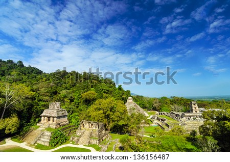 A wide view of Palenque featuring the main palace and several temples against a beautiful blue sky - stock photo
