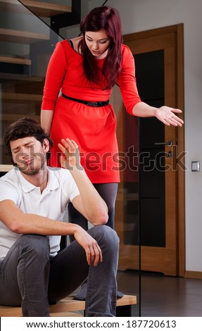 A wife standing over her husband complaining about his ignorance - stock photo