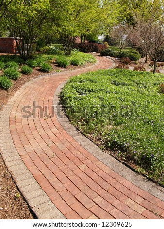 a winding brick path in a garden - stock photo
