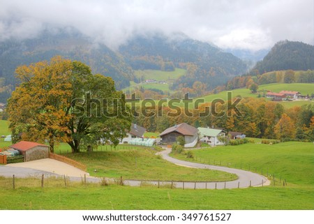 A winding country road curves between green fields and trees leading to a farmhouse on a beautiful autumn hillside ~ Autumn scenery of countryside in Ramsau, Bavaria Germany (Light version) - stock photo