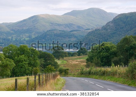 A winding road leads down to Thirlmere Lake as it nestles among the Cumbrian mountains in the English Lake District on an early autumn evening - stock photo