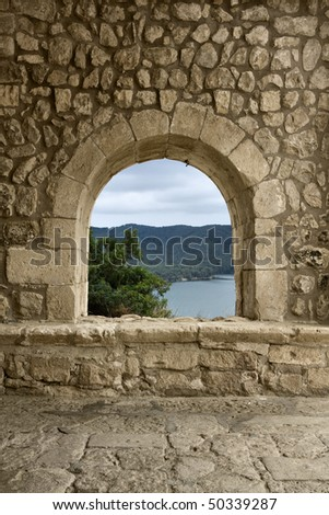 A window/arch at the entrance of a romanesque church in a spanish village. A beautiful landscape may be seen through it. - stock photo