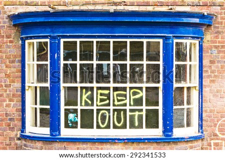 A window in a building for demolition, with warning graffiti - stock photo