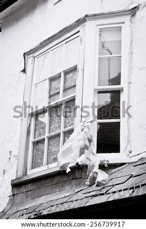 A window in an old house boarded up, in black and white - stock photo